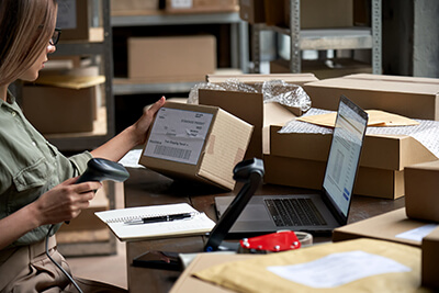 woman scanning box at desk with laptop in shipping warehouse