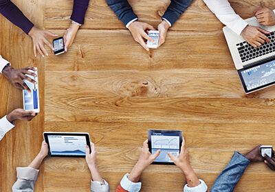 wooden table with business people hands holding various devices: cell phones, tablets, typing on laptop